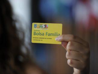A imagem mostra uma mulher segurando o cartâo do Bolsa Família