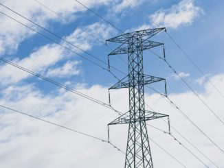 Torre de distribuição de energia com um céu azul com nuvens ao fundo